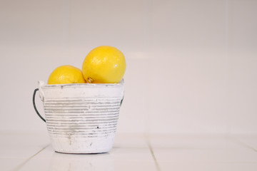 Yellow lemons in a small white bucket on a white background.