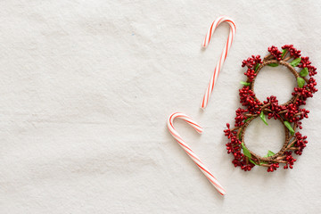 Candy canes and small wreaths on a white background.