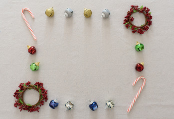 Christmas ornaments and candy canes arranged in a square.