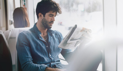 Young business man reading a newspaper while sitting in a city tramway beside a window. Bearded male with dark curly hair wearing light blue shirt going to the office by a public transport.