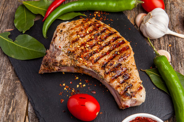 Grilled pork steak on the bone with seasonings and grilled tomatoes on a black background. Top view
