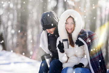 Smiling young couple with cups sititng in snow covered mountain forrest