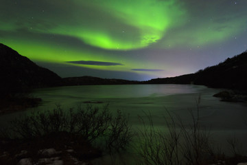 The Aurora in the night sky over hills and a frozen lake.