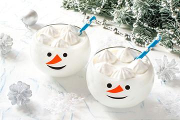 Banana milkshake with meringues in glasses in form of funny snowman