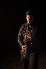 Man playing saxophone, with black background