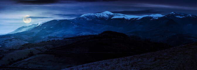 great mountain ridge Borzhava with snowy tops at night in full moon light. beautiful countryside landscape in late autumn
