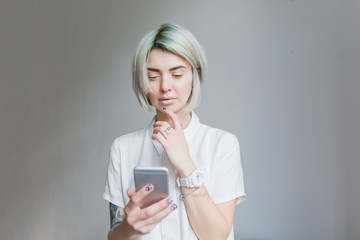 Portrait of cute  girl with gray short  hairstyle  standing on gray background. She wears white dress and light makeup, holds phone in hands.