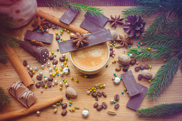 New Year's winter composition with coffee and spices in the kitchen on a wooden dinette and with pine branches. Beauty and inspiration with winter desserts.