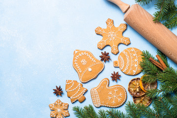 Christmas gingerbread cookies and spices on blue.