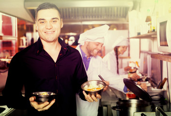 Chefs and happy waiter working