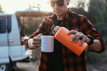 Trendy young man stands on camping site or on road stop in front of his camping van or camper with open trunk, pours coffee or tea from flask thermos in mockup cup to warm up