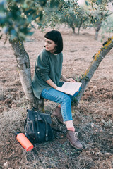 Beautiful young hipster woman or girl, adventurer or explorer sits on tree in park or garden with provence style atmosphere of french countryside, reads book or studies
