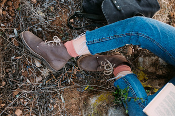 Close up of woman in raw hard blue denim jeans, pink socks and rough leather boots, sits on ground or tree trunk during adventure or hike, reads book during autumn vacation