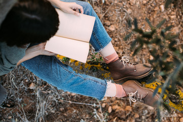 Over head top view shot of woman with brown hair looking through diary or mockup notebook, while in park or garden, sits on tree trunk day dreamer or student