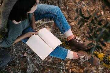 Soft focus shot of cute and beautiful young woman or girl student resting during hike or walk in park. Wears blue denim jeans, pink socks and brown leather boots, read book or notebook diary mockup