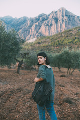 Attractive beautiful and cute natural beauty woman or young girl on hike through natural park with artisan hipster backpack, looks into camera, free and millennial, explores mountains
