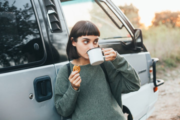 Cute young attractive female tourist drinks coffee or hot tea during rest stop in forest on hiking trip on road, leans on camper van and snacks on tasty cookie, concept camping and travel cup mockup