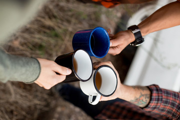 Group of friends enjoy hot beverage, coffee or tea during hiking or road trip, toast to more adventures and exploration in hipster millennial travel mugs or cups made of aluminum outdoors in park