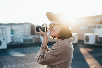 Cute adorable and trendy dressed in hipster outfit millennial young girl or woman makes photograph of sunset on vintage retro analog film camera, concept hobby and free time, happiness and chill