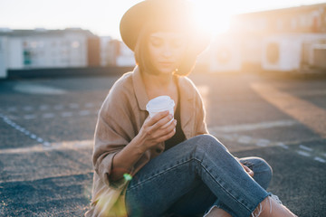 Beautiful trendy woman in cool outfit of hipster millennial, with fedora hat and glasses, sits on rooftop of big city, with sunset sunshine in background, holds take away to go coffee cup