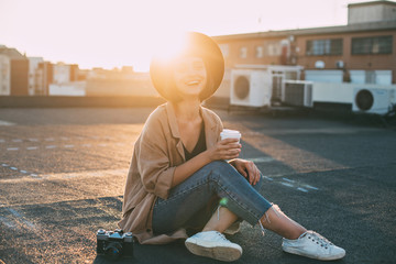 Happy trendy hipster woman in millennial cute outfit sits on ground at rooftop terrace, holds cup of take away coffee and looks into camera with smile, sunset light in her hair, concept forever young