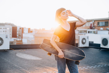 Cool and fashionable young hipster millennial woman stands on rooftop or street with longboard, sunset light flare, she poses, touches her hair, concept active youth and unconventional natural beauty