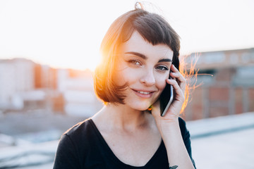 Portrait of young beautiful woman with short haircut, millennial hipster style outfit talking on phone, looks in camera with calm smile on face,  sunset light in back, smartphone through messaging app