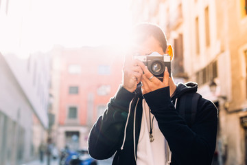 Sun flare sunset photo of male tourist or photographer making photo on analog vintage hipster film camera, with sun rays behind shoulder, concept millennial travel ideas and freedom nomad lifestyle
