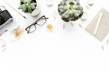 desk workspace with succulent, retro camera, diary, glasses and golden clips on white background. flat lay, top view