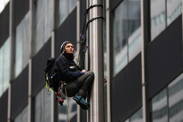 Activist from Rainforest Action Network (RAN) is seen on the flag pole in front of the headquarters of JP Morgan Chase, during the action of hanging a banner to protest the bank's investments, in New York