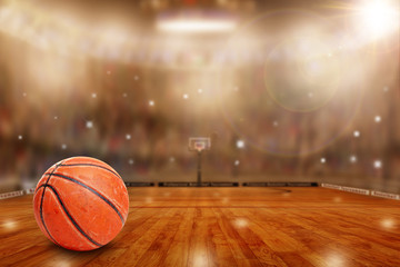 Fictitious basketball arena with ball on court and copy space. Camera flashes and lens flare special lighting effect on defocused background.