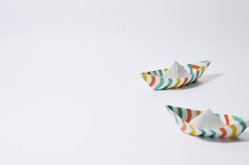colorful origami ships on white background