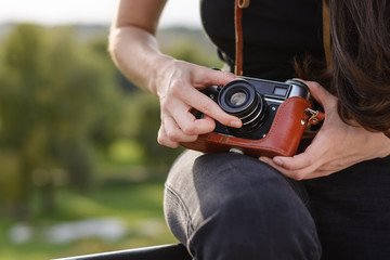 Young happy female photographer walks in the Park with retro camera