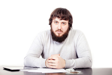 portrait of young businessman in beard, sitting in relaxed position at at office table with pleasant look. Confident male business person