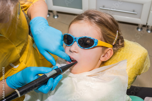 kid in dentist clinic Dental health  Female dentist curing a