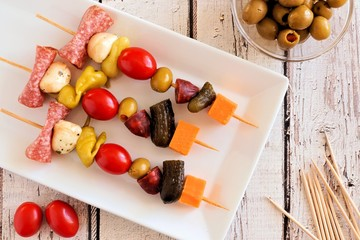 Spoed Fotobehang Voorgerecht Skewer appetizers with cheese, meat and pickles overhead view on a white wood background