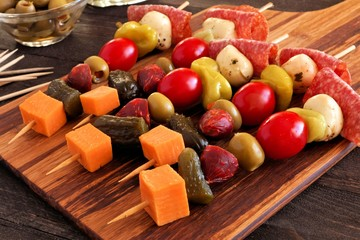 Skewer appetizers with cheese, meat and pickles close up table scene with wooden paddle board