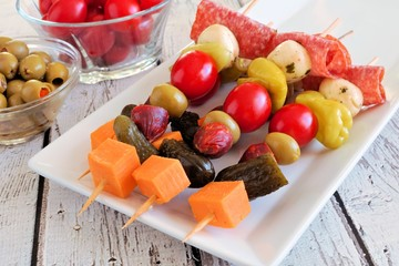 Skewer appetizers with cheese, meat and pickles close up table scene with white wood background