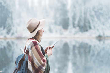 Handsome woman wearing poncho and backpack using mobile phone in first snow. Traveling among stunning winter landscape. Vacations in mountain wilderness. Wanderlust and boho style