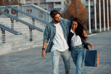 Young couple are walking after shopping in the city