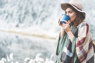 Young handsome woman with hot drink in hands spending vacations among stunning winter landscape. Traveling in mountains wilderness. Wanderlust and boho style