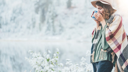 Pretty woman drinking hot coffee and enjoying vacations among stunning winter landscape. Traveling in mountains wilderness. Wanderlust and boho style