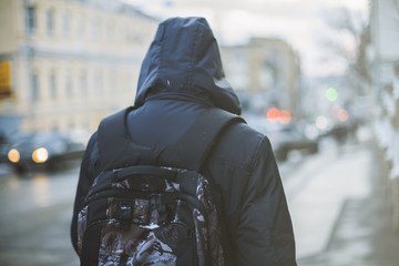 Student with backpack walking through foggy city street