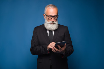Concentrate bearded senior using internet on a tablet and working in a comfortable way. Serious man in a glasses and modern strict suit