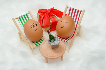 Funny lovely eggs in snow with gift box and bottle of wine