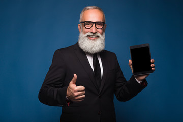 Happy bearded man in formal wear holds digital tablet and shows copy space on screen while standing on blue background. Empty place of screen of tablet. Man show with the screen of tablet and thumb up