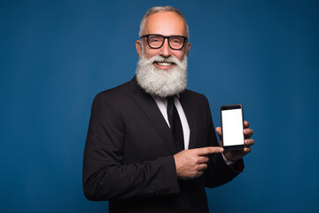 Happy bearded man in formal wear holds mobile phone and shows copy space on screen while standing on blue background. Empty place of screen of phone.