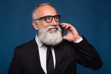 Happy smiling business bearded man with a smartphone talking on phone in a suit. Business conversation on phone with partner or manager