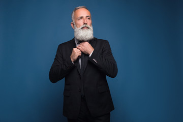 Bearded man in suit adjusts his tie
