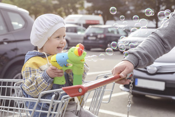 happy child sitting in a shopping cart with a toy and blowing bubbles